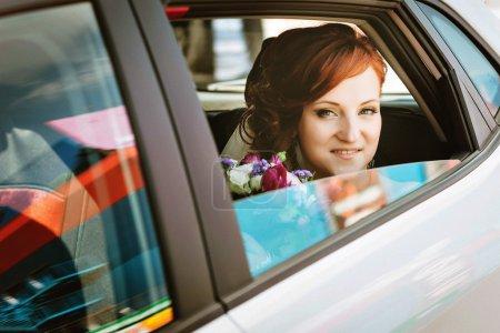 schöne Braut im Auto am Hochzeitstag mit Blick in die Kamera