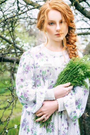 Portrait of a beautiful redhead girl in the spring garden