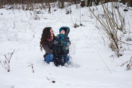 Mom and son in the winter forest.