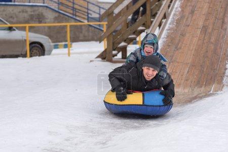 Photo pour Un jeune homme avec un garçon joyeux avec un tour de montagnes russes en hiver sur la glace. Beau papa et fils riant dans un parc d'hiver. Famille heureuse jouant avec la neige . - image libre de droit