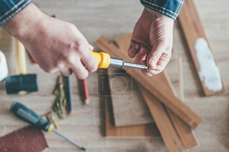 Carpenter holding screwdriver