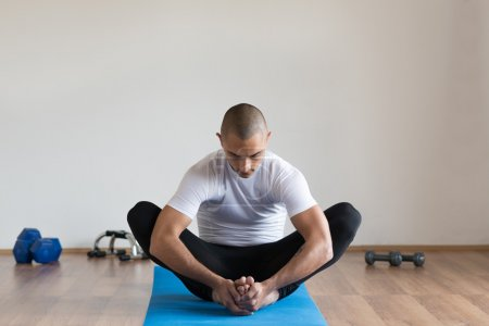 Sportsman  in sports clothes stretching after a workout.