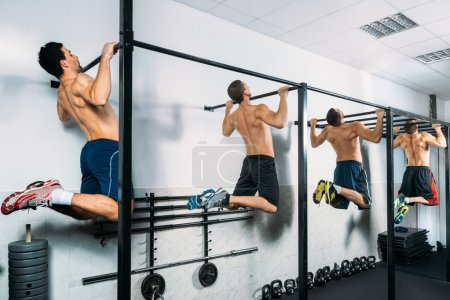 Group of Muscular Men Doing Pull Ups as part of Crossfit Training.