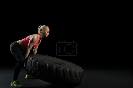 Photo for Muscular woman flip big tire as a part of Cross fit training. - Royalty Free Image