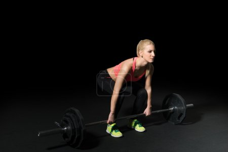 Crossfit woman athlete performs weight lift.