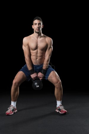 Man doing Kettle bell workout.