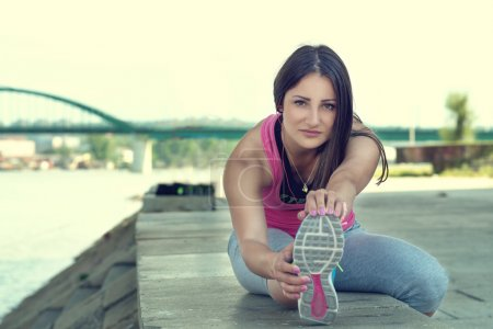 Woman doing  warm-up exercises before running.