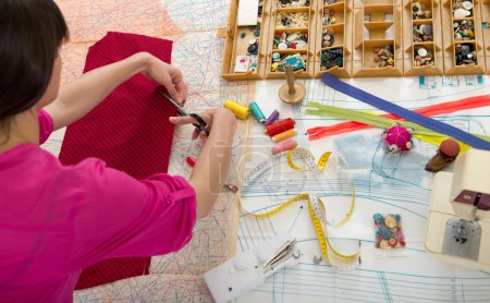 Photo for Young Woman sewing at home with sewing paper. - Royalty Free Image