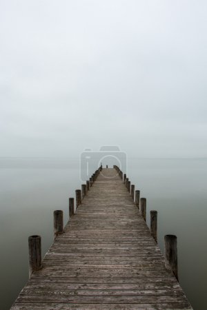 Photo for Deserted jetty, pier in foggy weather, vertical shot - Royalty Free Image