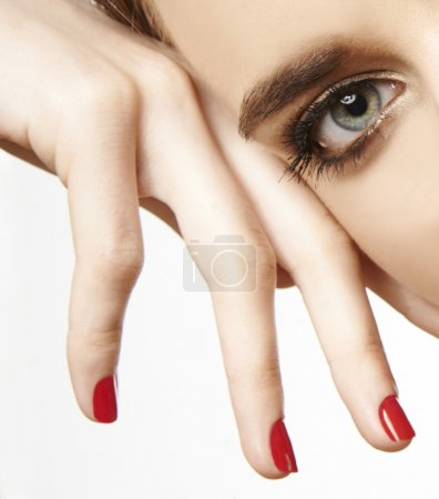 eye and hand with red nail polish