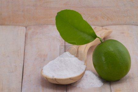 Baking soda in spoon and lemon fruit on wooden table