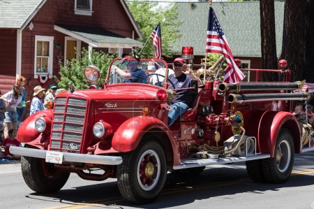 Photo for Graeagle, California, USA- July 5, 2015: Fireman from the Plumas Eureka fire district drive a fire engine in a parade smile and wave at the crowd during the Mohawk Valley Independence Day Celebration - Royalty Free Image