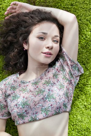 Young girl with curly hair lying on the floor on carpet, smiling and enjoying life. Tender feelings. Meditation. Practice yoga at home.