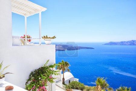 Photo pour Beau blanc grec maison typique avec différentes fleurs et de palmiers. Bord de mer de Thira, île de Santorini, Grèce - image libre de droit