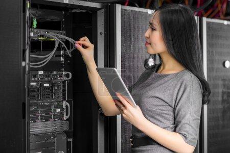 Photo pour Jeune ingénieur de femme d'affaires avec tablette en salle de serveur de réseau - image libre de droit