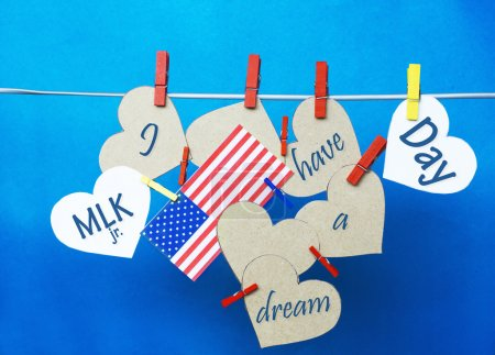 White  hearts - room for text,  USA ( America) flag hanging on colorful pegs ( clothespin ) on a line against a blue background.  United States of America.  Concept - Martin Luther King Day January 18. I have a dream collage.
