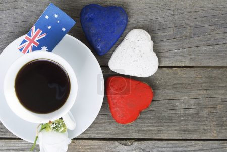 Heart shaped cookies red, white, blue.  cup of coffee (tea), Australia flag - decoration on old wooden table. notebook Happy Australia Day and koala. Sunny morning. Toned colored