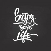 Enjoy your life- hand drawn lettering phrase isolated on the chalkboard background Fun brush ink inscription for photo overlays greeting card or t-shirt print poster design