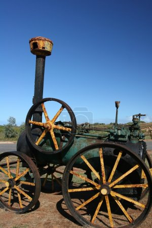 Historic black and green rusty Steam Engine Tractor at Carnarvon harbour und stunning blue sky.
