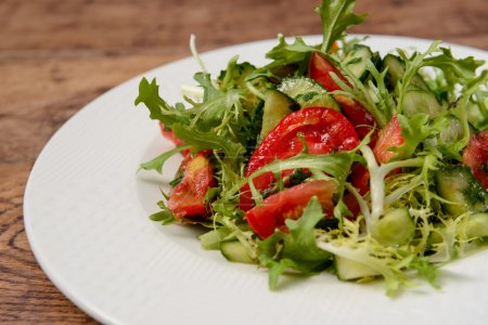 Vegetable salad in white round plate on wooden table. Macro.