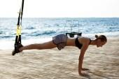 Mladá dívka sportovní výcvik s trx moře ráno