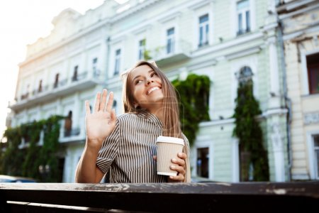 Young beautiful girl sitting on bench, holding coffee, smiling.