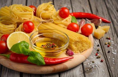 Pâtes, légumes, herbes et épices pour la cuisine italienne sur la table rustique en bois .
