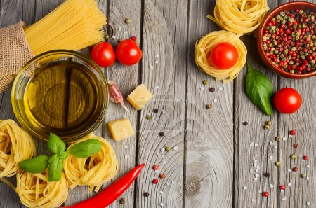 Pasta, vegetables, herbs and spices for Italian food on the rustic wooden table.
