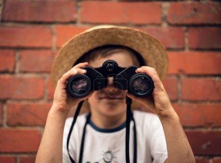 Boy in a straw hat looks in binoculars