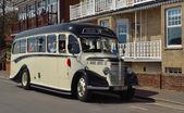 Vintage krémové a černé Bedford autobus jede ulicí