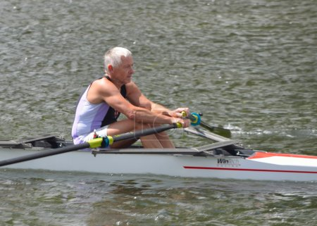 Older man in sculling competition on the river Ouse.