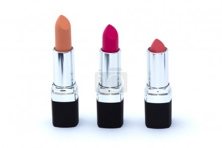 Three pink lipsticks in black case isolated on white
