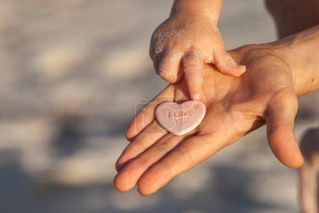Photo pour Mains de mère et de l'enfant sur la plage dans la partie des Caraïbes, du Mexique, Riviera Maya. Fond de plage l'été. - image libre de droit