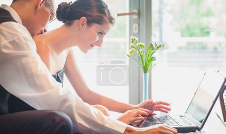Photo for Well dressed caucasian couple, 25-30 searching internet together. - Royalty Free Image