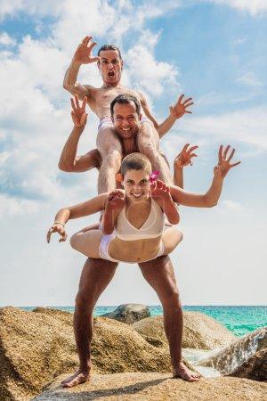 Photo pour Membres de l'équipe effectuant humoristique position Acro Yoga - image libre de droit