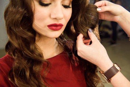 Photo pour Coiffeur fait fille coiffure avec les cheveux longs dans un salon de beauté. Créer des boucles avec des fers à friser. Soins capillaires professionnels - image libre de droit