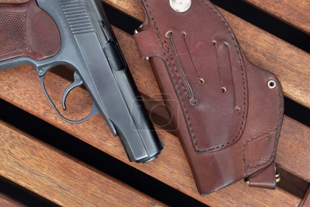 The Makarov pistol and holster lie on wooden boards.