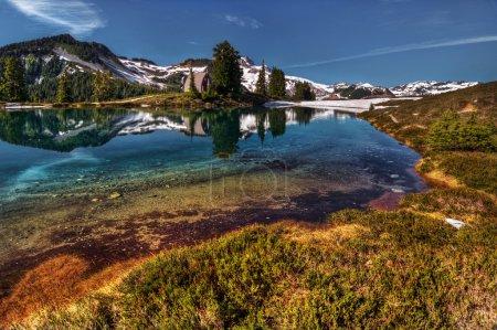 Photo pour Courbure du rivage du lac de montagne avec réflexion parfaite, ciel bleu et montagnes lointaines - image libre de droit