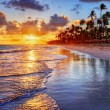 Beautiful sunrise at a beach-side resort with palm...