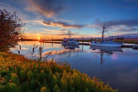 Boats at cloudy sunrise at marina