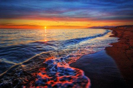 Photo pour Vague se brisant sur une plage de sable au lever du soleil - image libre de droit