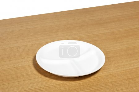 the wood desk(table) with white dish isolated white.