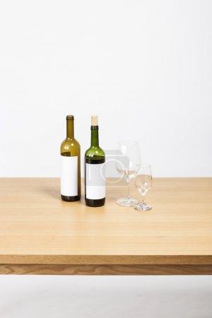 the wood desk(table) with wine bottle and glasses isolated white.