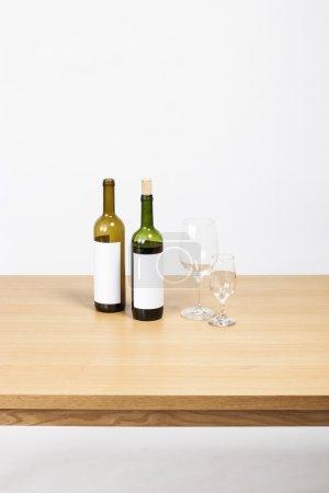 Photo pour Le bureau en bois (table) avec deux bouteilles de vin vert jaunes et des verres isolés blancs . - image libre de droit
