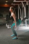 Dívka squat v tělocvičně s váhami