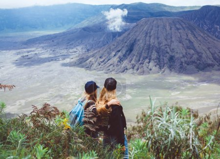 women standing looking  at volcano