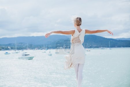 Photo for Young beautiful girl posing on the pier in ballet flats and a bright dress - Royalty Free Image