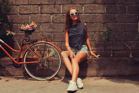 Girl  posing with red bicycle