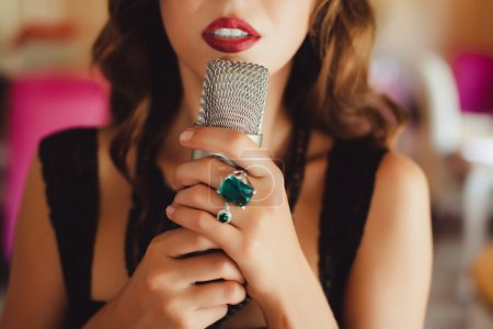 Beautiful girl singing into a microphone in the ro...