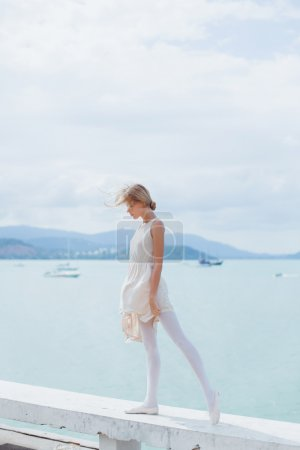 Girl posing on the pier in ballet flats